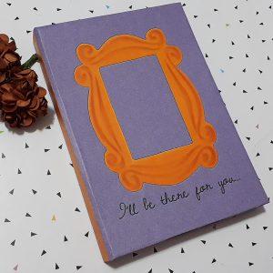 """Foto de um caderno tamanho A6 de capa roxa com leve textura na impressão. Sua estampa mostra uma moldura amarela como a do seriado n qual é inspirada e em baixo se lê a frase 'I'll be there for you..."""""""