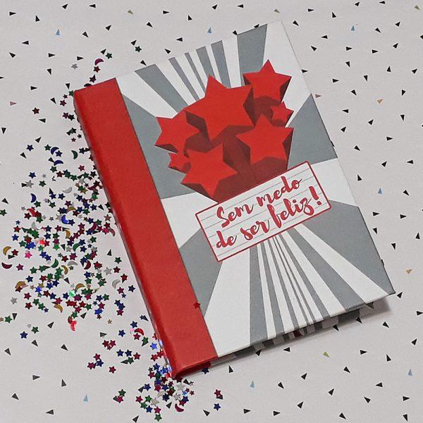 """Caderno artesanal tamanho A6 com capa de listras em cinza e branco, uma chuva de estrelas vermelhas para cima com um quadrado simulando folha de caderno na frente onde se lê a frase 'Sem medo de ser feliz"""", lombada simulando couro da cor vermelha."""